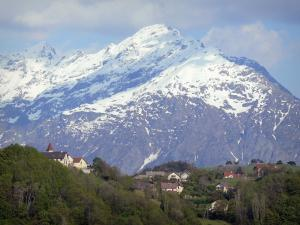 Landscapes of Dauphiné - Village surrounded by trees and dominated by a snow-capped mountain