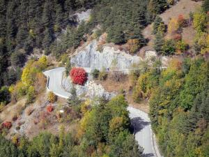 Landscapes of Dauphiné - Oisans - Road of L'Alpe d'Huez: winding road (turn) bordered by trees with autumn colors