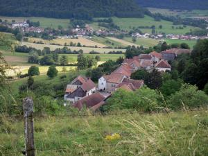 Landscapes of the Doubs - Fence of a meadow in foreground, houses of a village, fields, prairies and trees