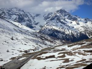 Landscapes of the Hautes-Alpes - Road leading to the Col du Lautaret pass and mountains dotted with snow; in the Écrins National Nature Park