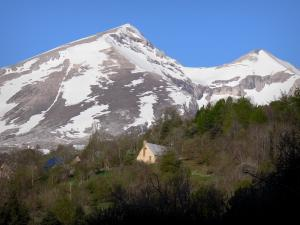 Landscapes of the Hautes-Alpes - Dévoluy mountain range: houses surrounded by trees and mountain dotted with snow