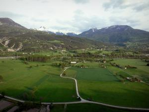 Landscapes of the Hautes-Alpes - Durance valley: prairies, fields, road, Durance river lined with trees and snowy mountain tops (snow)
