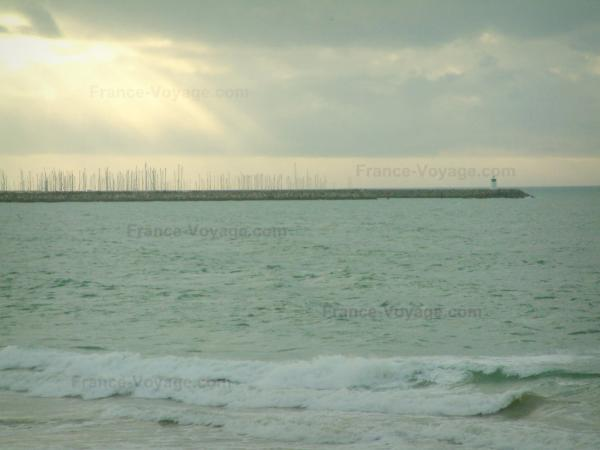 Landscapes of the Loire-Atlantique coast - Sea (Atlantic Ocean), sailboats, lighthouse and turbulent sky with sunbeams