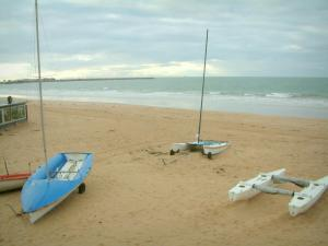 Landscapes of the Loire-Atlantique coast - Sandy beach with boats, sea (Atlantic Ocean) and turbulent sky