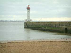 Landscapes of the Loire-Atlantique coast - Sandy beach and the Vieux Môle lighthouse in Saint-Nazaire, sea (Atlantic Ocean), coast in background and cloudy sky