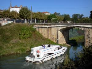 Landscapes of the Lot-et-Garonne - Bridge spanning the Garonne Canal, boat sailing on the waters of the canal, trees, houses, and bell tower of the church overlooking the place; in Damazan