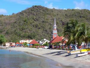 Landscapes of Martinique - Fishing village of Anse d'Arlet at the edge of the Caribbean Sea, with its church steeple, its houses and its sandy beach
