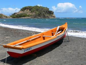 Landscapes of Martinique - Fishing boat on the beach of Santa Maria overlooking the islet of Santa Maria and the Atlantic Ocean