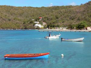 Landscapes of Martinique - View of the jetty from the fishing village of Anse d'Arlet and turquoise sea dotted with boats