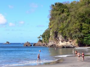Landscapes of Martinique - Lazing on the beach of Anse Ceron with holidaymakers bathing in the calm waters of the sea