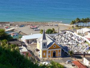 Landscapes of Martinique - View of the village of Grand'Rivière the edge of the Atlantic Ocean, with its church Sainte-Catherine, its cemetery and its fishing port