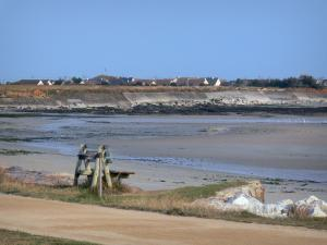 Landscapes of Normandy - Coast of the Cotentin peninsula: bench with view of the beach, roofs of houses in background