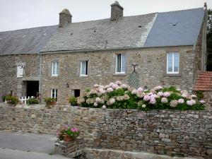 Landscapes of Normandy - Stone house of a village in the Cotentin peninsula, flowers