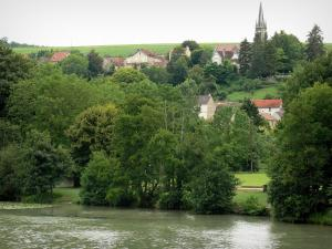 Landscapes of Picardy - Marne valley: Marne river, bank planted with trees, houses and bell tower of the Mont-Saint-Père church