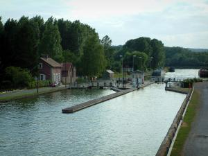 Landscapes of Picardy - Side canal of the Oise river with a lock, moored barges, banks and trees of a forest