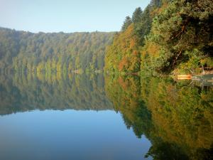 Landscapes of the Puy-de-Dôme - Auvergne Volcanic Regional Nature Park: Pavin lake surrounded by trees with autumn colours, in the Sancy mountains (Monts Dore)