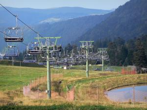 Landscapes of the Puy-de-Dôme - Auvergne Volcanic Regional Nature Park: chairlift (ski lift) of the ski resort of Le Mont-Dore, grass and trees in the Massif du Sancy mountains (Monts Dore)