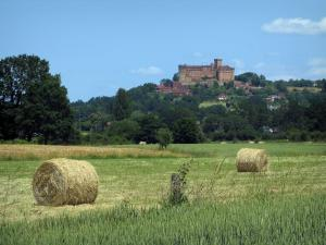 Landscapes of the Quercy - Castelnau-Bretenoux castle, houses, trees and field with straw bales