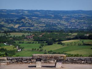 Landscapes of the Quercy - Stone bench with view of fields, prairies, houses, trees and small hills