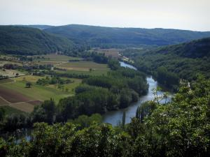Landscapes of the Quercy - Trees in foreground with view of the River Lot, trees along the water, fields and hills, in the Lot valley