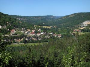 Landscapes of the Quercy - Trees in foreground with view of the houses of a village and hills