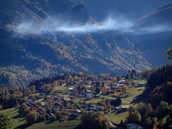 Landscapes of the Savoie in automn - Houses of a village, trees in autumn and mountains covered with forests
