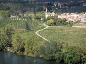 Landscapes of the Tarn-et-Garonne - Garonne valley: River Garonne, trees along the water, fields, church and houses of the village of Espalai