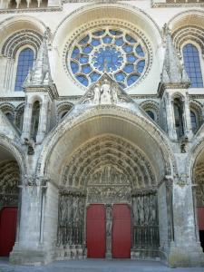 Laon - West facade of the Notre-Dame cathedral of Gothic styla: carved portal topped with a rose window