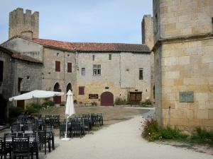 Larressingle - Café terrace, crenellated tower and facades of houses in the fortified medieval village