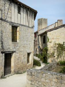 Larressingle - Alley lined with stone houses and crenellated tower in the background