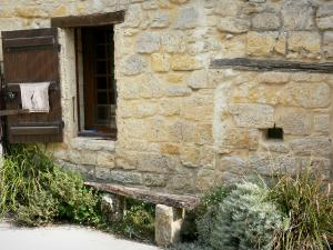 Larressingle - Facade of a stone house, bench and plants