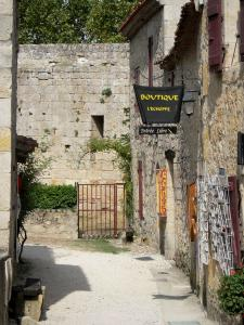 Larressingle - Alley of the fortified medieval village, with shop  and stone houses