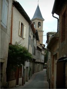 Lautrec - Narrow street lined with houses and view of the bell tower of the Saint-Rémy collegiate church