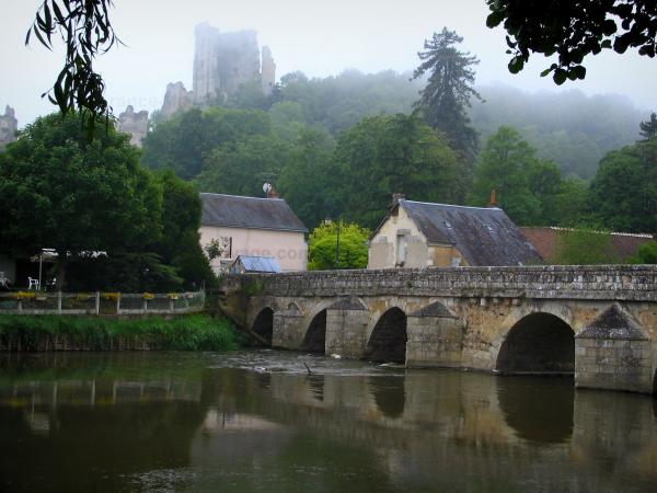 Lavardin - Gothic bridge spanning the Loir River, houses of the village, trees and ruins of the Château dominating the set