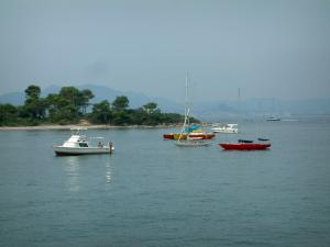 Lérins island - Sainte-Marguerite island: sea with boats, beach, pines trees and coast of the French Riviera in background