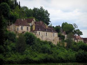 Limeuil - Houses of the medieval village, trees and cloudy sky, in Périgord