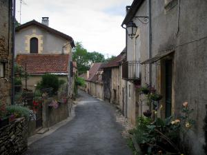 Limeuil - Flower-bedecked street of the medieval village and its houses, in Périgord