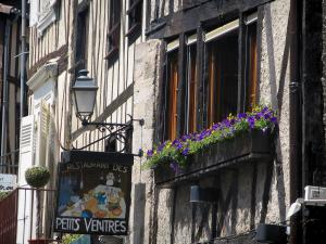 Limoges - Facade of a half-timbered house in the Boucherie street with flower-bedecked windows, lamppost and shop sign (banner) of a restaurant