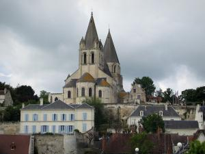 Loches - Saint-Ours collegiate church of Romanesque style, houses of the city and cloudy sky