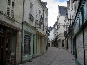 Loches - Street of the old town and its houses with facades decorated with lampposts and with forged iron shop signs