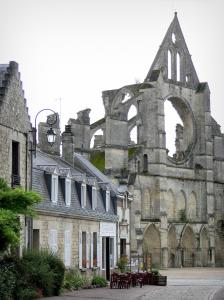 Longpont - Facade of the old abbey church of Gothic style, cafe terrace and houses in the village