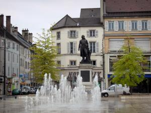 Lons-le-Saunier - Liberté square: statue of General Lecourbe, fountain with jets, shops and building facades
