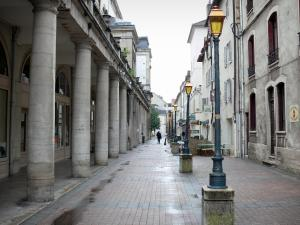 Lons-le-Saunier - Ronde street with the columns of the theatre, lampposts, shops and facades of houses