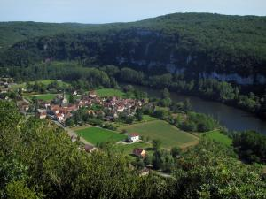 Lot valley - Church and houses of a village, fields, trees by the River Lot, cliffs and forest, in the Quercy