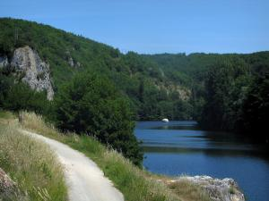 Lot valley - Road lined with high flora leading to the bank, Lot river with a boat and trees along the water, in the Quercy