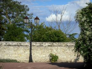 Loudun - Lamppost, stone wall, trees and cloudy sky