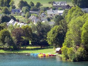 Louron valley - Génos-Loudenvielle lake, colourful moored paddle boats, bank lined by trees and houses overhanging the set