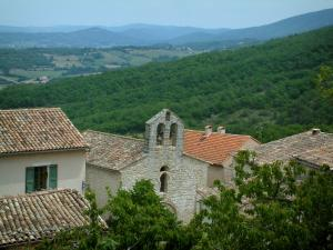 Luberon - Houses and church in a village with a forest and hills in background