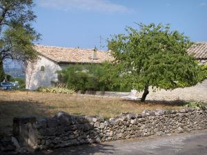 Lussan - Small stone wall, house and trees