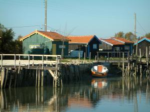 Marennes - Cayenne port: channel, moored boat and huts in the oyster port